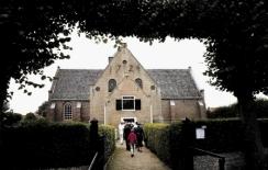 Kerkgangers op zondag ochtend lopen naar de ingang van de protestantse st Maartenskerk in Oosterend op Texel voor de gereformeerde dienst. Voor serie over nederlandse identiteit. FOTO: BRAM BUDEL